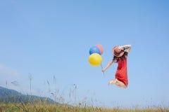Mujer feliz que salta y que sostiene el globo con el cielo azul al aire libre Imagen de archivo