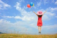 Mujer feliz que salta y que sostiene el globo con el cielo azul al aire libre Foto de archivo