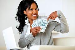 Mujer feliz que señala el un montón de dinero del efectivo Foto de archivo