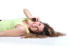Mujer feliz que se acuesta y que ríe en el teléfono móvil Imagen de archivo libre de regalías