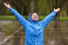 Mujer feliz que se coloca con los brazos extendidos en lluvia Imagen de archivo libre de regalías