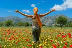 Mujer feliz que se coloca en campo colorido de la flor Foto de archivo