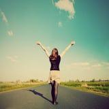 Mujer feliz que se coloca en el camino vacío. Estilo retro del vintage Fotografía de archivo
