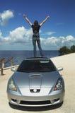 Mujer feliz que se coloca en la azotea del coche Fotografía de archivo