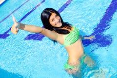 Mujer feliz que se coloca en muestra aceptable linda sonriente de la piscina foto de archivo libre de regalías
