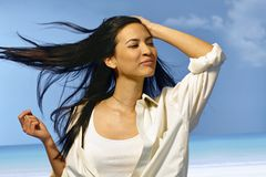 Mujer feliz que se coloca en viento del verano Fotos de archivo