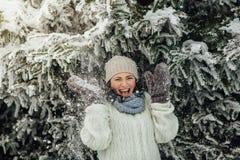 Mujer feliz que se divierte con la nieve que cae de árboles Imagen de archivo libre de regalías