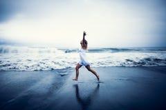 Mujer feliz que se ejecuta en la playa imagenes de archivo