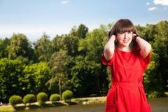 Mujer feliz que se reclina en el parque Imagenes de archivo