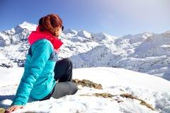 Mujer feliz que se relaja en el top de la montaña debajo del cielo azul con luz del sol en el día de invierno soleado, vacaciones Imagenes de archivo
