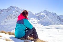 Mujer feliz que se relaja en el top de la montaña debajo del cielo azul con luz del sol en el día de invierno soleado, vacaciones Fotografía de archivo