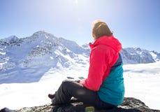 Mujer feliz que se relaja en el top de la montaña debajo del cielo azul con luz del sol en el día de invierno soleado, vacaciones Foto de archivo libre de regalías
