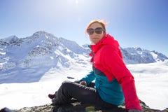 Mujer feliz que se relaja en el top de la montaña debajo del cielo azul con luz del sol en el día de invierno soleado, vacaciones Fotografía de archivo libre de regalías