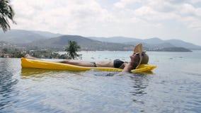 Mujer feliz que se relaja en un colchón inflable amarillo en piscina almacen de metraje de vídeo