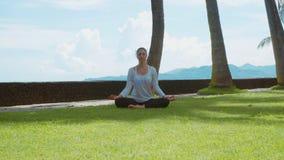 Mujer feliz que se relaja practicando la yoga, el mudra gyan y la posición de loto, meditando, respecto a la playa del océano de