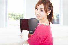 Mujer feliz que se sienta con el ordenador portátil Fotos de archivo