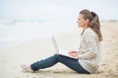 Mujer feliz que se sienta con el ordenador portátil en la playa fría Imagen de archivo