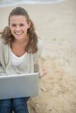 Mujer feliz que se sienta con el ordenador portátil en la playa fría Foto de archivo libre de regalías