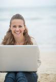 Mujer feliz que se sienta con el ordenador portátil en la playa fría Foto de archivo