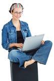 Mujer feliz que se sienta con la computadora portátil Foto de archivo libre de regalías