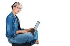 Mujer feliz que se sienta con la computadora portátil Imagenes de archivo
