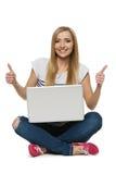Mujer feliz que se sienta con la computadora portátil que muestra el pulgar encima de muestras Fotos de archivo libres de regalías