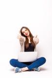 Mujer feliz que se sienta con la computadora portátil que muestra el pulgar encima de muestras Imagen de archivo