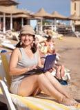 Mujer feliz que se sienta con la computadora portátil en la playa Imagen de archivo