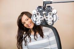 Mujer feliz que se sienta detrás de Phoropter imagen de archivo libre de regalías