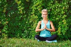 Mujer feliz que se sienta en actitud de la yoga del padmasana Foto de archivo libre de regalías