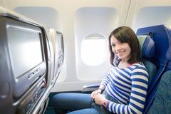 Mujer feliz que se sienta en aeroplano fotografía de archivo
