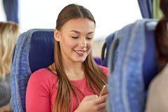 Mujer feliz que se sienta en autobús del viaje con smartphone Imagenes de archivo