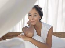Mujer feliz que se sienta en cama Imagen de archivo