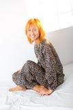 Mujer feliz que se sienta en cama Foto de archivo