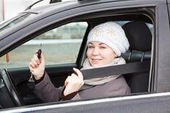 Mujer feliz que se sienta en coche Fotos de archivo