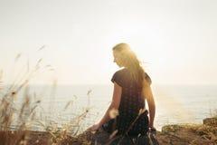 Mujer feliz que se sienta en el acantilado en fondo de la puesta del sol imagenes de archivo
