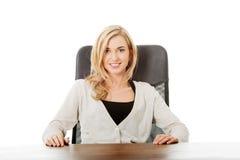 Mujer feliz que se sienta en el escritorio Imagen de archivo libre de regalías