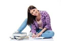 Mujer feliz que se sienta en el piso y que escribe en cuaderno Fotos de archivo libres de regalías