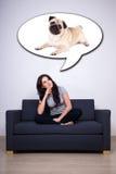 Mujer feliz que se sienta en el sofá y que piensa o que sueña sobre perro Foto de archivo