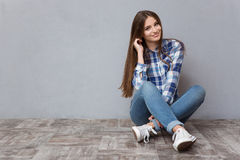 Mujer feliz que se sienta en el suelo Imagenes de archivo
