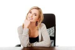 Mujer feliz que se sienta en la barbilla conmovedora del escritorio fotos de archivo