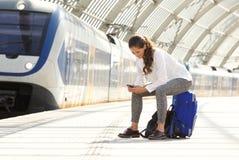 Mujer feliz que se sienta en la maleta usando el teléfono móvil Imagenes de archivo