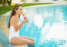 Mujer feliz que se sienta en la piscina y el cóctel de consumición Imágenes de archivo libres de regalías