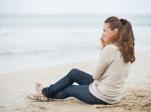 Mujer feliz que se sienta en la playa sola y el teléfono móvil que habla Fotos de archivo