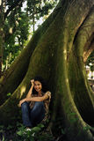 Mujer feliz que se sienta en la sombra de un árbol Fotografía de archivo libre de regalías