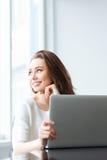 Mujer feliz que se sienta en la tabla con el ordenador portátil Fotos de archivo libres de regalías