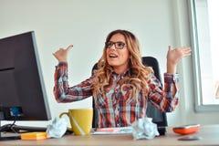 Mujer feliz que se sienta en su escritorio con los brazos para arriba imagen de archivo libre de regalías
