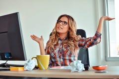 Mujer feliz que se sienta en su escritorio con los brazos para arriba foto de archivo