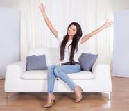 Mujer feliz que se sienta en un júbilo del sofá Imágenes de archivo libres de regalías