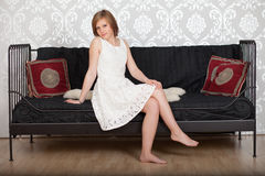 Mujer feliz que se sienta en un sofá Fotografía de archivo libre de regalías